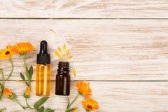 Το ουσιαστικό πετρέλαιο Aromatherapy με marigold ανθίζει στο άσπρο υπόβαθρο με το διάστημα αντιγράφων για το κείμενό σας Τοπ όψη Στοκ φωτογραφία με δικαίωμα ελεύθερης χρήσης