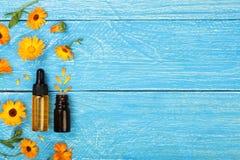 Το ουσιαστικό πετρέλαιο Aromatherapy με marigold ανθίζει στο μπλε υπόβαθρο με το διάστημα αντιγράφων για το κείμενό σας Τοπ όψη Στοκ φωτογραφία με δικαίωμα ελεύθερης χρήσης