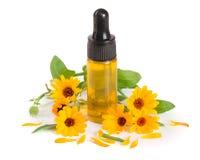 Το ουσιαστικό πετρέλαιο Aromatherapy με marigold τα λουλούδια απομόνωσε το άσπρο υπόβαθρο Στοκ Εικόνα