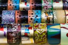 Το λουστραρισμένο με λάκκα βραχιόλια στενό επάνω υπόβαθρο σχεδίων Στοκ Φωτογραφία
