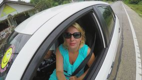 Το οδηγώντας αυτοκίνητο και η γυναίκα ανδρών κοιτάζουν από το παράθυρο αυτοκινήτων φιλμ μικρού μήκους