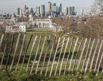 Το πάρκο του Γκρήνουιτς - ένας φράκτης και ψηλά κτίρια του Canary Wharf στοκ εικόνες
