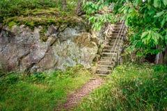 Το πέτρινο κλιμακοστάσιο εξαφανίζεται σε ένα πολύβλαστο πράσινο δασικό Odderoya, Kristiansand, Νορβηγία στοκ εικόνες