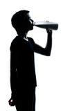 το πίνοντας κορίτσι αρμέγει μια νεολαία εφήβων σκιαγραφιών Στοκ Φωτογραφίες