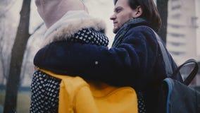 Το πίσω ευτυχές χαλαρωμένο καυκάσιο νέο ρομαντικό ζεύγος άποψης στα περιστασιακά χειμερινά ενδύματα περπατά μαζί να αγκαλιάσει μι απόθεμα βίντεο