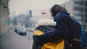 Το πίσω ευτυχές χαλαρωμένο νέο ρομαντικό ζεύγος άποψης στα περιστασιακά θερμά ενδύματα περπατά μαζί να αγκαλιάσει μια χιονώδη κρύ φιλμ μικρού μήκους