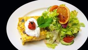 Το πίτα και η σαλάτα που ολοκληρώνονται από μια πορτοκαλιά φέτα, άσπρο πιατάκι απομονώνουν Στοκ Εικόνα