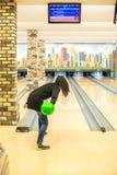 Το παίζοντας μπόουλινγκ γυναικών ρίχνει μια σφαίρα στη λουρίδα στοκ εικόνες