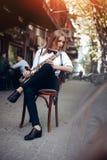 Το παίζοντας νέο ελκυστικό κορίτσι στο άσπρο πουκάμισο με μια συνεδρίαση saxophone caffe πλησίον ψωνίζει - υπαίθριος σε sity Προκ Στοκ φωτογραφία με δικαίωμα ελεύθερης χρήσης