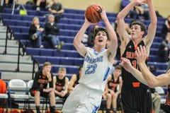 Το παίχτης μπάσκετ γυμνασίου Varsity ανεβαίνει για ένα καλάθι  φρουρημένος από τον αντίπαλο στοκ φωτογραφία με δικαίωμα ελεύθερης χρήσης