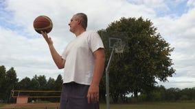 Το παίχτης μπάσκετ κάνει ταχυδακτυλουργίες τη σφαίρα καλαθοσφαίρισης απόθεμα βίντεο