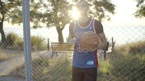 Το παίχτης μπάσκετ στέκεται με τη σφαίρα στο δικαστήριο, που περιμένει το παιχνίδι Σε σε αργή κίνηση Το καλύτερο πορτρέτο φορέων φιλμ μικρού μήκους