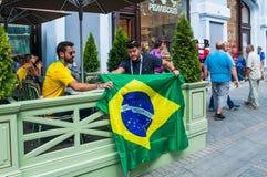 Το Παγκόσμιο Κύπελλο της FIFA του 2018 Βραζιλιάνοι ανεμιστήρες με τη σημαία της συνεδρίασης της Βραζιλίας στον υπαίθριο καφέ στην Στοκ Φωτογραφία