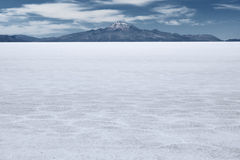 Το παγκόσμιο μεγαλύτερο αλατισμένο επίπεδο και κοιμισμένο ηφαίστειο Tunupa στο μακρινό υπόβαθρο στοκ φωτογραφίες