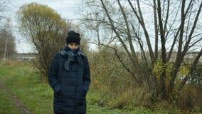 Το παγωμένα σακάκι και το μαντίλι φθινοπώρου κοριτσιών ` s είναι μεταξύ των δέντρων απόθεμα βίντεο