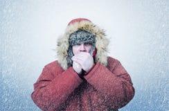 Το παγωμένο άτομο το χειμώνα ντύνει τα θερμαίνοντας χέρια, κρύο, χιόνι, χιονοθύελλα