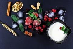 Το παγωμένο σμέουρο, βατόμουρο, φράουλες, φύλλα μεντών πιάτων γιαουρτιού, κομμάτια του πάγου σε έναν μαύρο σχιστόλιθο επιβιβάζετα Στοκ Φωτογραφίες