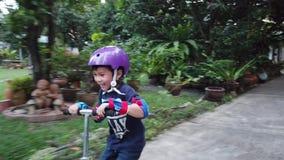 Το παιδάκι μαθαίνει να οδηγά ένα μηχανικό δίκυκλο με την πλήρη προστασία φιλμ μικρού μήκους