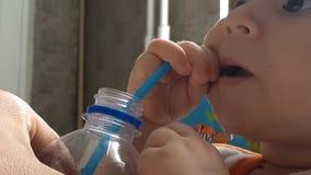 Το παιδάκι πίνει whater από το πλαστικό μπουκάλι με τον πλαστικό σωλήνα απόθεμα βίντεο