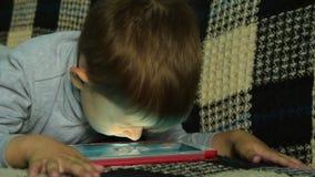 Το παιδάκι πρόκειται να παίξει στο PC ταμπλετών φιλμ μικρού μήκους
