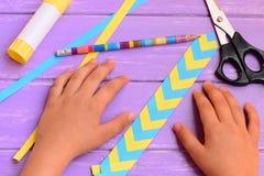 Το παιδί έκανε έναν σελιδοδείκτη από το κίτρινο και μπλε διπλωμένο έγγραφο Το παιδί παρουσιάζει χρωματισμένο έγγραφο σελιδοδείκτη Στοκ Φωτογραφία