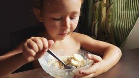 Το παιδί έχει το πορτρέτο προγευμάτων λίγου χαριτωμένου κοριτσιού τρώει το κουάκερ απόθεμα βίντεο