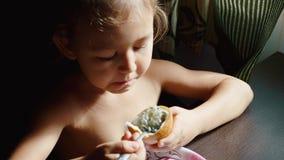 Το παιδί έχει το πορτρέτο προγευμάτων λίγου χαριτωμένου κοριτσιού τρώει το λωτό απόθεμα βίντεο