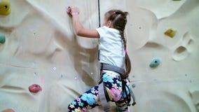 Το παιδί αναρριχείται σε έναν ειδικό τοίχο για την ορειβασία το κορίτσι επτά ετών στον εξοπλισμό ασφάλειας συμμετέχει στο βράχο απόθεμα βίντεο