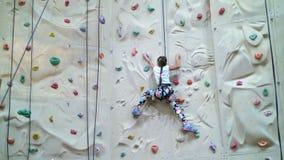 Το παιδί αναρριχείται σε έναν ειδικό τοίχο για την ορειβασία το κορίτσι επτά ετών στον εξοπλισμό ασφάλειας συμμετέχει στο βράχο φιλμ μικρού μήκους