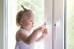 Το παιδί ανοίγει το παράθυρο με την κλειδαριά Προστασία από να πέσει έξω chi Στοκ Φωτογραφία