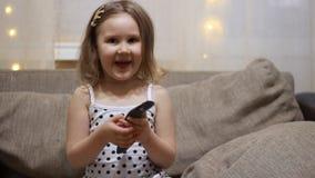 Το παιδί ανοίγει τη TV χρησιμοποιώντας το μακρινό Τηλεόραση προσοχής κοριτσάκι απόθεμα βίντεο