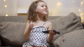 Το παιδί ανοίγει τη TV χρησιμοποιώντας το μακρινό Τηλεόραση προσοχής κοριτσάκι φιλμ μικρού μήκους