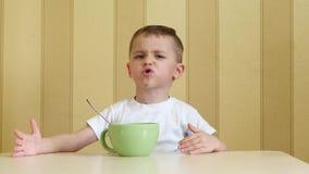 Το παιδί απαιτεί τα εύγευστα τρόφιμα, το αγόρι δεν συμπαθεί τα τρόφιμα, χειρονομίες με τα χέρια του, παρουσιάζει συγκινήσεις φιλμ μικρού μήκους