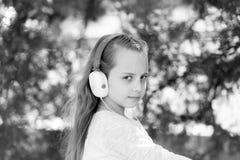 Το παιδί απολαμβάνει τη μουσική στα ακουστικά υπαίθρια Το μικρό κορίτσι ακούει μουσική στο θερινό πάρκο Παιδί μόδας και σύγχρονη  Στοκ Φωτογραφία