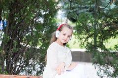 Το παιδί απολαμβάνει τη μουσική στα ακουστικά υπαίθρια Παιδί μόδας και σύγχρονη τεχνολογία Το μικρό κορίτσι ακούει μουσική στο θε Στοκ φωτογραφία με δικαίωμα ελεύθερης χρήσης