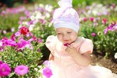 το παιδί απολαμβάνει το κορίτσι λουλουδιών λίγα στοκ εικόνες