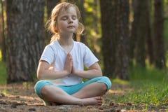 Το παιδί ασκεί τη γιόγκα στο δάσος στοκ φωτογραφία