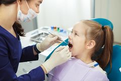 Το παιδί βρίσκεται στην καρέκλα οδοντιάτρων και περνά από τη διαδικασία στοκ φωτογραφίες