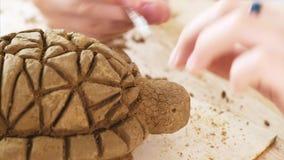 Το παιδί γρατσουνίζει τη σύσταση των κλιμάκων στο χειροποίητο παιχνίδι χελωνών από τον άργιλο φιλμ μικρού μήκους