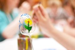 Το παιδί δίνει το αυγό Πάσχας γυαλιού ζωγραφικής με το ζωηρόχρωμο λουλούδι στοκ εικόνες