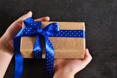 Το παιδί δίνει το δεμένο τόξο σε ένα κιβώτιο δώρων σε ένα μαύρο υπόβαθρο στοκ φωτογραφία