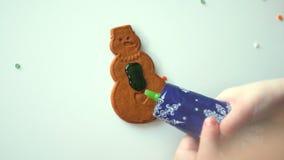 Το παιδί διακοσμεί τα μπισκότα Χριστουγέννων απόθεμα βίντεο