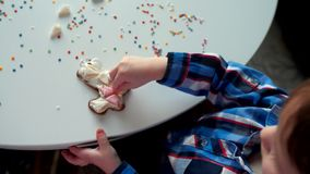 Το παιδί διακοσμεί τα μπισκότα Χριστουγέννων φιλμ μικρού μήκους
