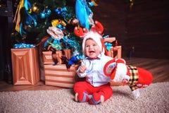Το παιδί είναι ευτυχές μια εορταστική ημέρα κοντά στο χριστουγεννιάτικο δέντρο στοκ φωτογραφία