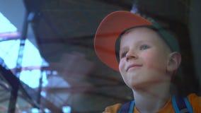 Το παιδί εξετάζει μέσω του γυαλιού τον αερολιμένα, χαμόγελα και τα κύματα, το αγόρι συναντιούνται, βλέπουν από κάποιο στον αερολι απόθεμα βίντεο