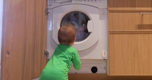 Το παιδί εξετάζει το πλυντήριο απόθεμα βίντεο