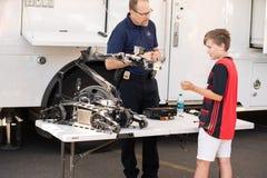 Το παιδί εξετάζει το ρομπότ εκτελεστικών αποσπασμάτων στοκ φωτογραφία με δικαίωμα ελεύθερης χρήσης