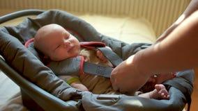 Το παιδί επέστρεψε από έναν περίπατο Ο πατέρας παίρνει έξω το μωρό από το κάθισμα αυτοκινήτων, ξεσφίγγει τις ζώνες ασφαλείας Το π απόθεμα βίντεο