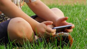 Το παιδί 6 ετών βάζει σε μια χλόη με τη συσκευή απόθεμα βίντεο