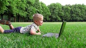 Το παιδί 6 ετών βάζει σε μια χλόη με το lap-top φιλμ μικρού μήκους